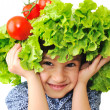 Kid with salad and tomato hat on his head, fake hair made of vegetables — Stock Photo