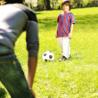 Cute little boy with his father playing with a ball in beautiful park in na — ストック写真