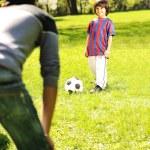 menino bonitinho com o pai dele jogando com uma bola no belo parque em at — Foto Stock