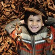 Close-up portrait of an beautiful autumn child laying on ground — Stock Photo