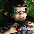 Cute positive boy with glasses and binoculars laying on ground and smiling — Stock Photo