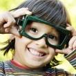 Very positive boy holding his big funny glasses and smiling, outdoor — Stock Photo