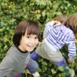 Happy childhood outdoor, happy faces between the leaves of the trees in for - Stock Photo