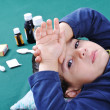 Stock Photo: Sick child with medics and pills behind him