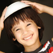 Cute kid with dish on head smiling — Stock Photo #6150640