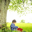 Happy children reading the book under the tree — Stock Photo