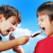 Two kids feeding each other ice cream — Stock Photo
