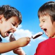 Two kids feeding each other ice cream — Stock Photo #6150669