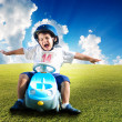 Happy kid on green meadow driving a car — Stock Photo #6150670