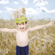 Cute kid in wheat meadow with wheat crown on head — Lizenzfreies Foto