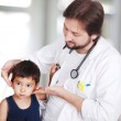 Young doctor examining little boy in hospital — Stock Photo