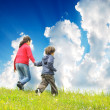 Stock Photo: Happy children running on madow with beautiful sky against them