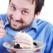 Young man eating cake — Stock Photo
