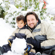 Stock Photo: Father and son playing happily in snow making snowman, winter season