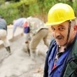 Elderly menager on workplace with workers on fresh concrete — Stock Photo