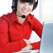 Beautiful Customer Representative with headset smiling during a telephone c — Stock Photo
