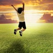 Stock Photo: Happy child jumping on green meadow