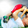 A parent and his kid laying and smiling on grass — Stock Photo