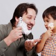 Man in bathroom putting shaving cream on young boy's face — Stock Photo