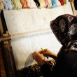 Woman working at the loom. Oriental Muslim national crafts. Focus on the fa - Стоковая фотография
