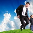 Father and son jumping outdoor on green meadow — Stock Photo #6151153