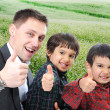 Young father and two sons outdoor sitting and rising thumb up — Stock Photo