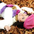 图库照片: Close-up portrait of an beautiful autumn woman laying on ground