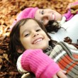 Close-up portrait of an beautiful autumn woman and kid laying on ground — Stock Photo