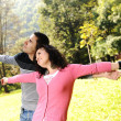 Two young relaxed in nature with opened arms looking up and breathin — Stock Photo
