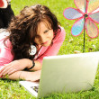 Happy young girl laying on green grass in nature and working on laptop — Stock Photo