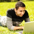 Happy young man laying on green grass in nature and working on laptop — Stock Photo