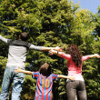 Stock Photo: Young happy family in nature with opened arms looking up and breathing fres