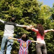 Young happy family in nature with opened arms looking up and breathing fres — Stock Photo