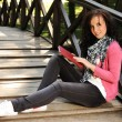 Young beautiful girl student sitting on wooden bridge in nature and reading — Foto de stock #6151244