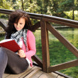 Young beautiful girl student sitting on wooden bridge over the bridge  in n - Stock Photo