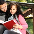 Young couple, girl and boy sitting in park and reading a book - Stock Photo