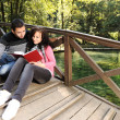 Young couple, girl and boy sitting in park and reading a book — Stock Photo