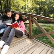 Stock Photo: Young couple, girl and boy sitting in park and reading book