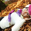 Young beauty girl laying on autumn ground and leaves, perfect face and natu — Stock Photo