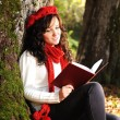 Beauty gorgeous autumn girl sitting in nature beside the tree and reading t — Stock Photo