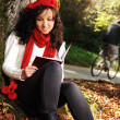 Beauty gorgeous autumn girl sitting in nature beside the tree and reading t - Photo