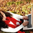 Beauty gorgeous autumn girl sitting in nature beside the tree and working o — Foto Stock
