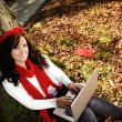 Beauty gorgeous autumn girl sitting in nature beside the tree and working o - Foto de Stock