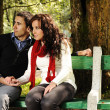 Young couple in nature sitting on bench, male and female together — Stock Photo