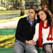 Young couple in nature sitting on bench, male and female together — Stock Photo #6151313