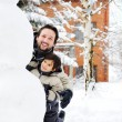 Father and son playing happily in snow making snowman, winter season — Stock Photo