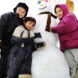 Children playing happily in snow making snowman, winter season - Stock Photo