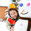 Winter snowman, snow show and happy funny young man who made him — Stock Photo