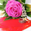 Love rose, for lover, on white with affiance (marriage) rings and red heart — Stockfoto
