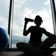 Fitness sporty girl silhouette excercising and drinking a water — Stock Photo